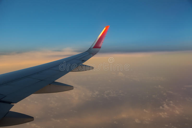 Flying above clouds. Lying above clouds and the end of the daytime royalty free stock photography