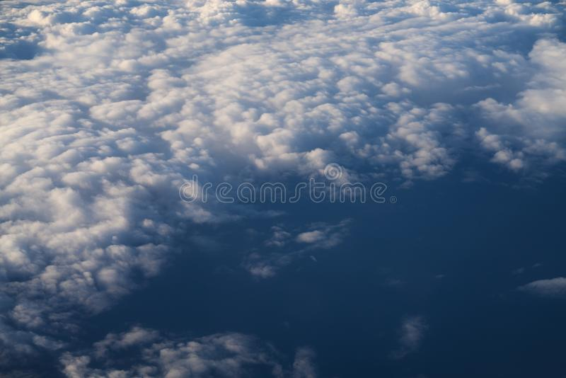 Flying above the clouds in midday. Skyscape stock photo