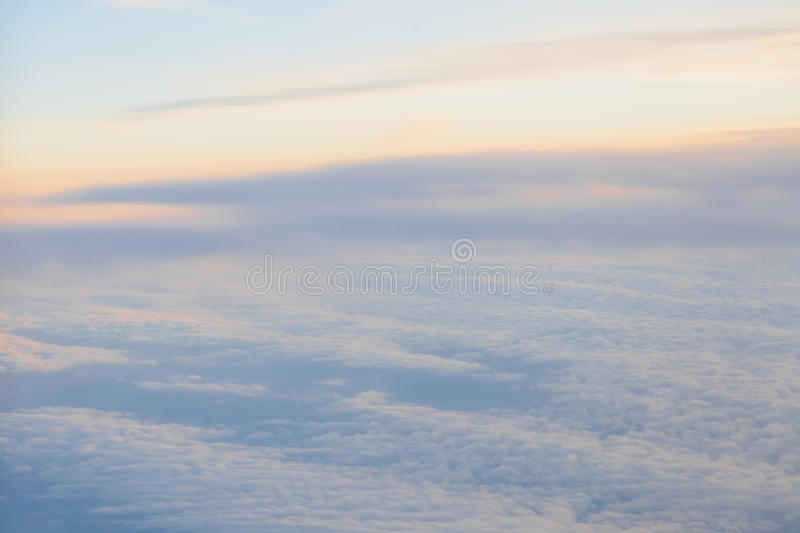Flying above the clouds at sunset landscape from an airplane stock photo