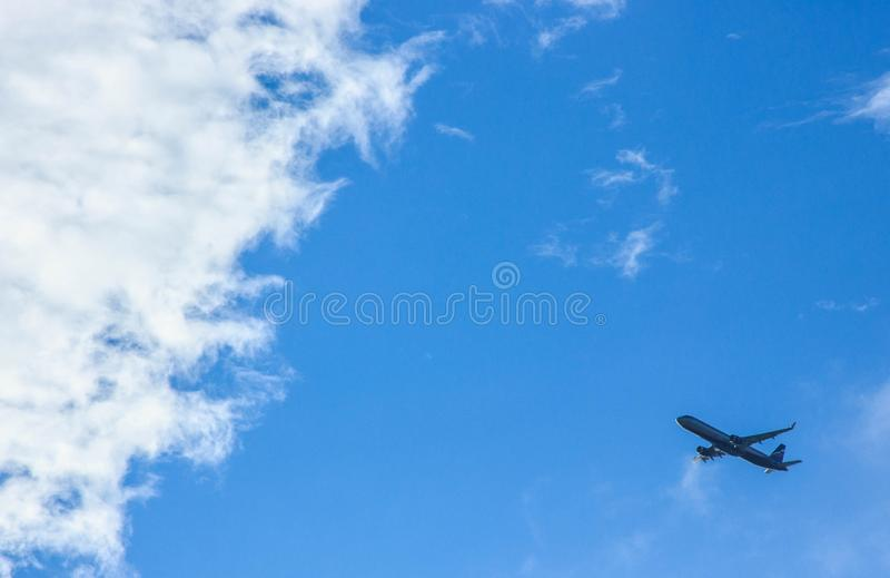 A flying airplane in the skies royalty free stock photos