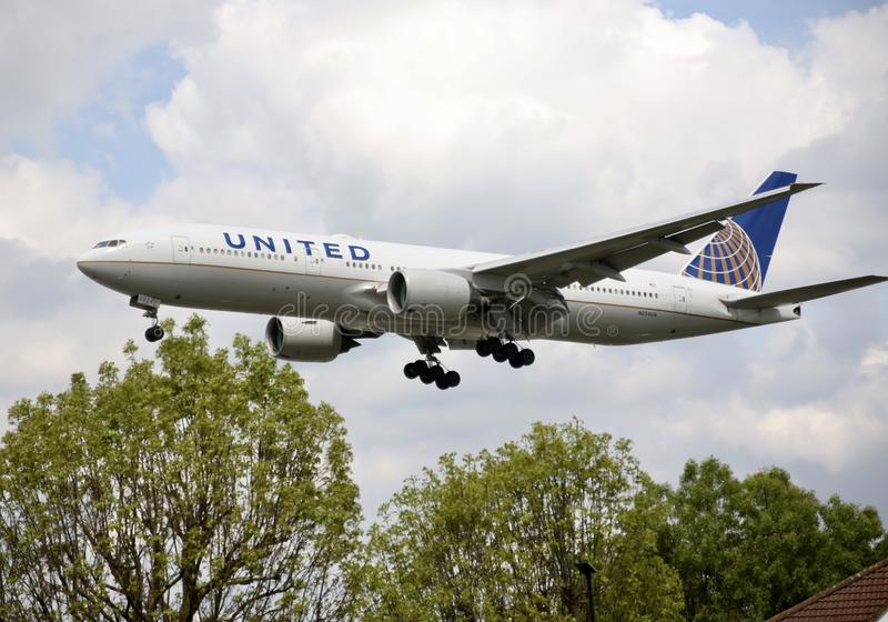 A flying airplane of United Airlines. Landing toward heathrow airport. Boeing 777 stock photo