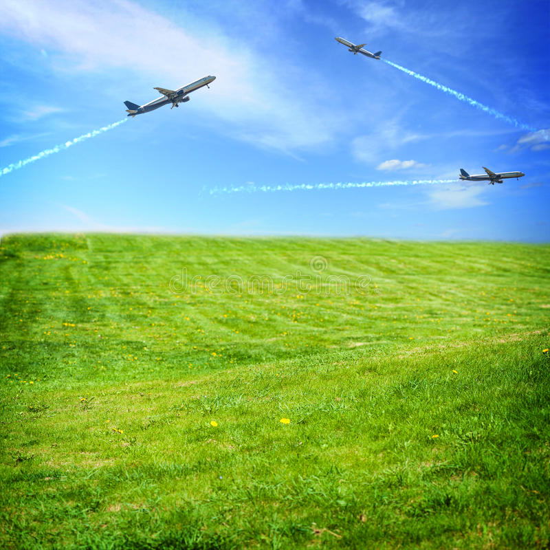 Flying airplanes in blue sky. Fresh green grass on a summer field and flying airplanes in blue sky stock photo