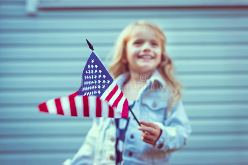 Flying american flag in little girl's hand. Selective focus. Blurred background. Independence Day, Flag Day concept. Vintage and retro colors. Instagram stock photography