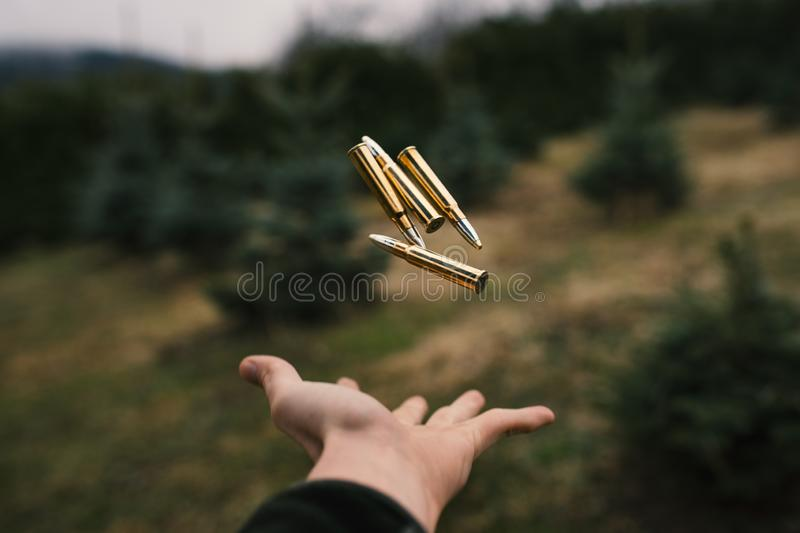 Flying ammunition above a man hand. Professional hunter and ammunition for hunting. Caliber 8x57. Concept of industry. stock image