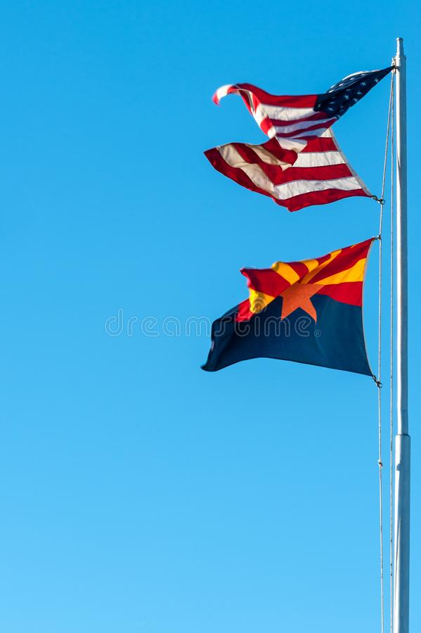 Arizona state and USA flags. Flying Arizona state and USA flags on the flagpole against blue sky background royalty free stock images
