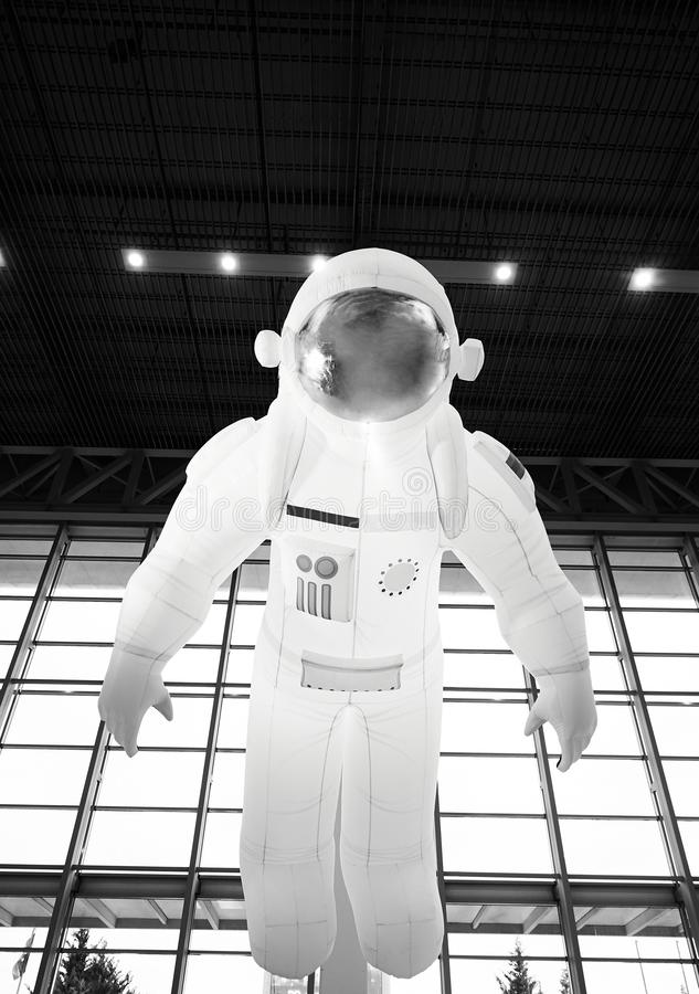 Flying astronaut by the window on background, indoors. Inflatable spaceman royalty free stock images