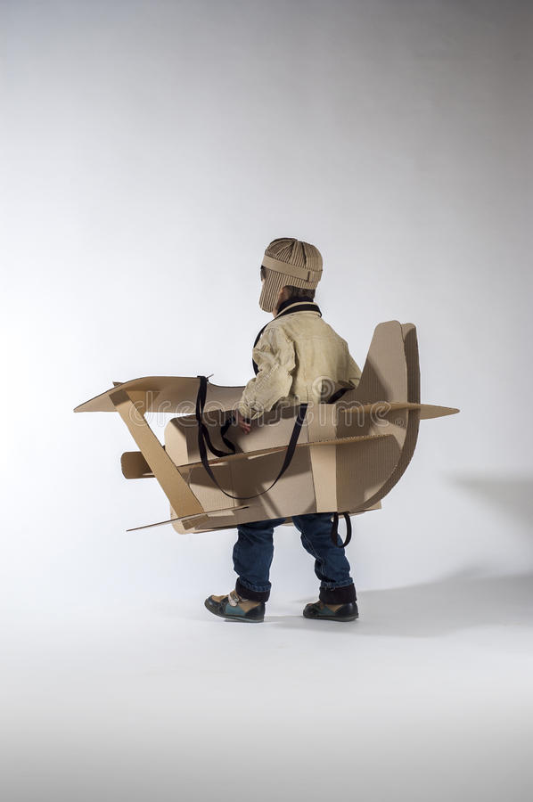 Flying away. Child is flying away on hand made cardboard plane. Back view stock photos