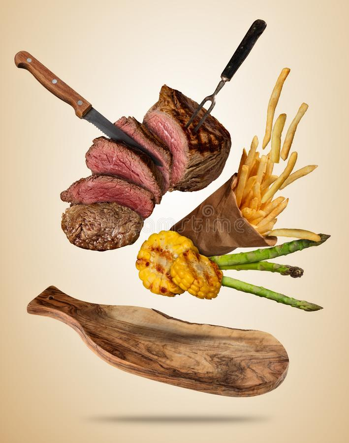 Flying beef steaks with grilled vegetable and french fries serve royalty free illustration