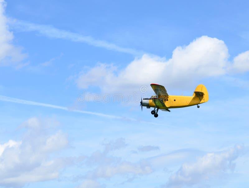 Flying biplane. Against blue sky stock photos