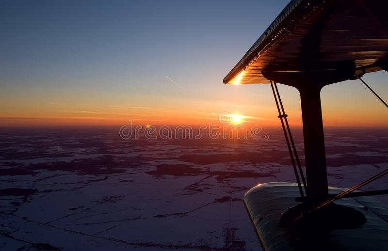 Flying a biplane at sunset. Flying on a biplane an-2 at sunset royalty free stock photos