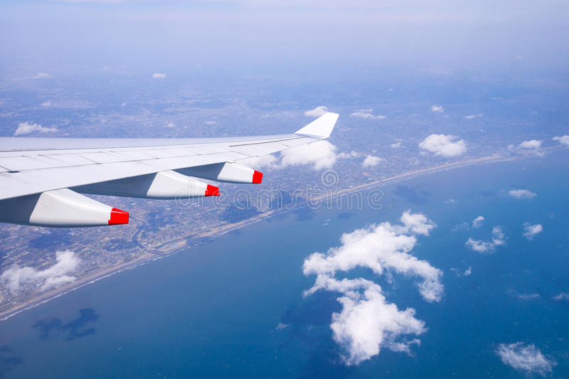 Flying into blue sky and sea beach and Wing of airplane with sky royalty free stock images