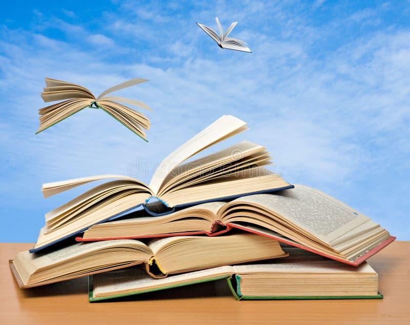 Flying books. Books flying away from shelf stock images