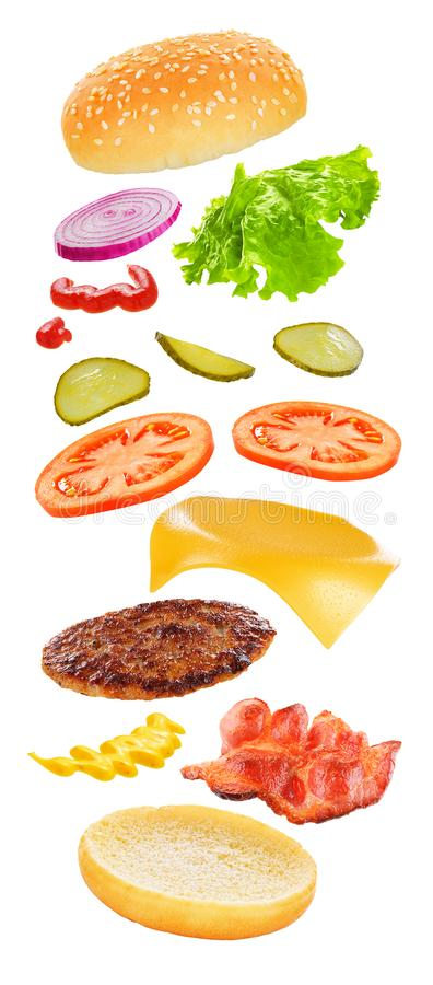 Flying burger isolated. Flying ingredients of burger with cheese, bacon, pickles, tomato, onions and lettuce isolated on white background stock photos
