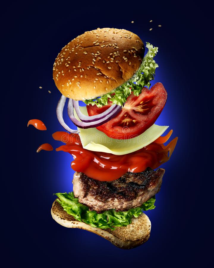 Flying burger with sesame seeds. Green salad, ketchup, tomato slices and onions on a blue background royalty free stock image