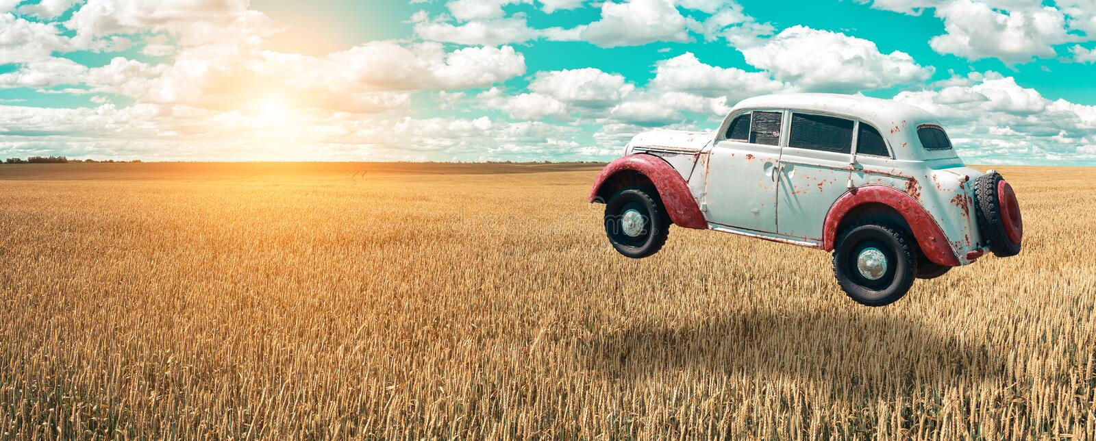 Flying car soars into the sky. Retro automobile hovers in the air above a golden wheat field on the background of blue sky. Flying car soars into the sky. Retro royalty free stock photo