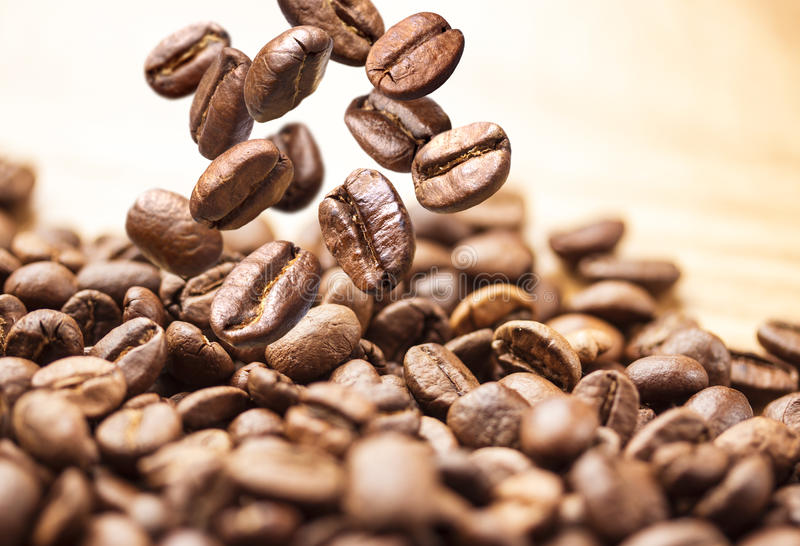 Flying coffee beans. Coffee beans falling on pile isolated on white background royalty free stock photo