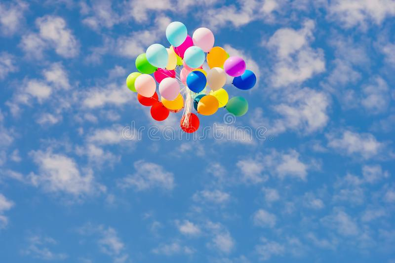 Flying colorful toy balloon on a blue sky stock photography