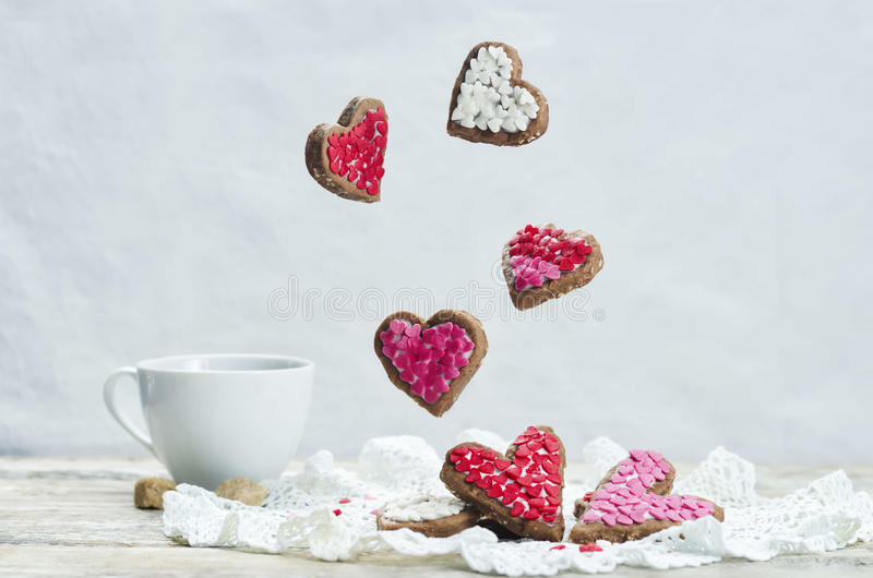 Flying cookies in the forms of hearts stock image