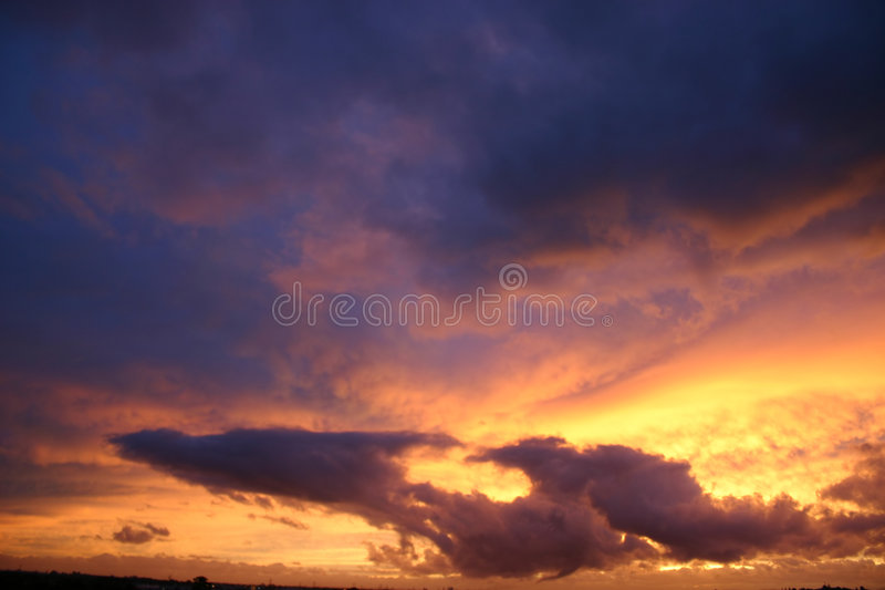Flying dragon cloud. A cloud shaped like a flying dragon at sunset stock photos