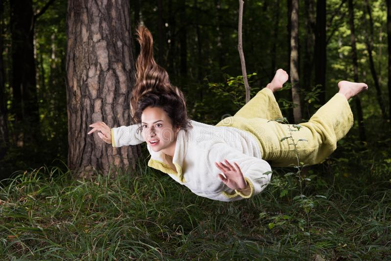 Flying in a dream. Young woman in pajamas in summer green forest. In a state of weightlessness. Wonder what he saw and not to believe their eyes royalty free stock photo