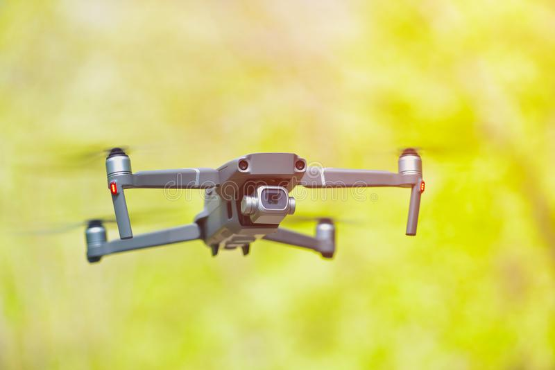 Flying drone with camera hovering inside a forrest, natural background.  stock photos