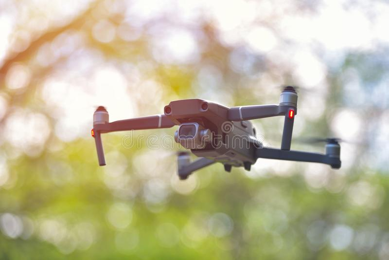 Flying drone with camera hovering inside a forrest, natural background.  stock image