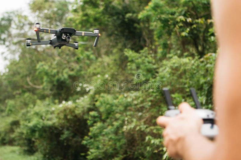Flying drone on focus and blurred hands holding a control remote man in a field royalty free stock photos