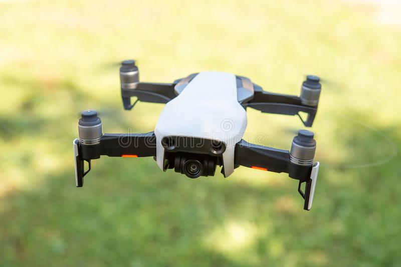 Flying drone with video camera with blurred green background royalty free stock images