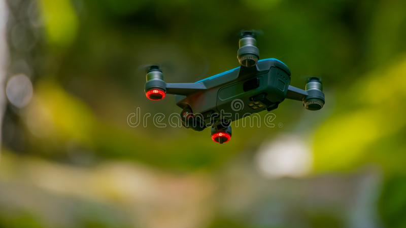 Flying drones on green background blurred. Flies, greens, aerials, cameras, technologies, copters, aircrafts, digitals, outdoors, backgrounds, quadcopters royalty free stock image