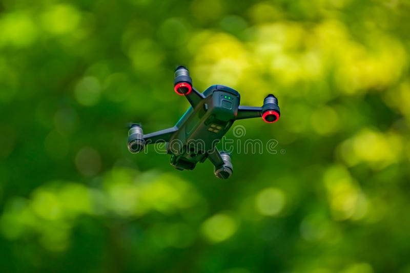 Flying drones on green background blurred. Flies, greens, aerials, cameras, technologies, copters, aircrafts, digitals, outdoors, backgrounds, quadcopters stock photo