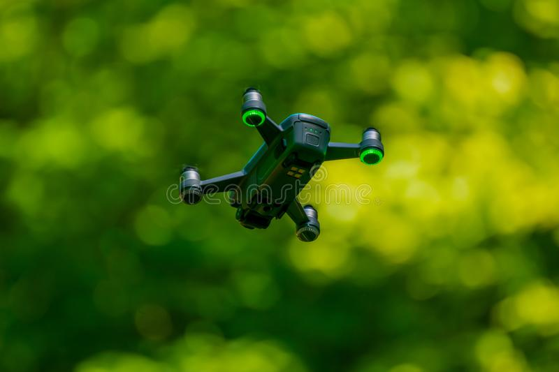 Flying drones on green background blurred. Flies, greens, aerials, cameras, technologies, copters, aircrafts, digitals, outdoors, backgrounds, quadcopters royalty free stock images