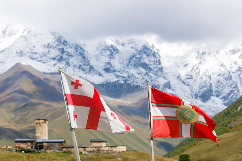 Flying flag of Georgia and flag of Georgian Border Police. With Svan`s tower and mountains on the background, Svaneti. royalty free stock photos