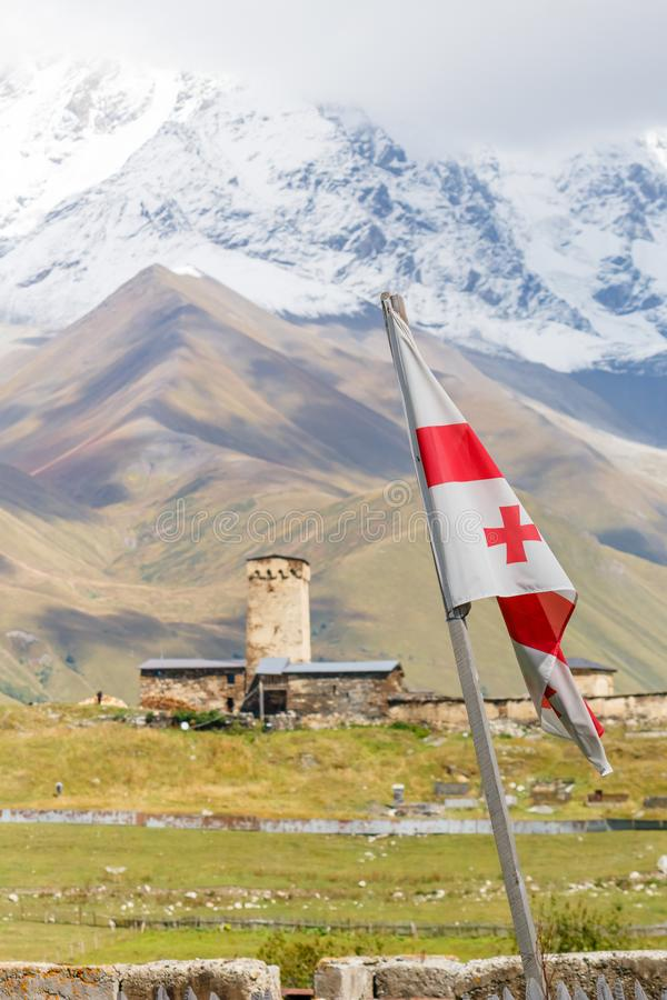 Flying flag of Georgia with Svan`s tower and mountains on the background, Ushguli, Mestia, Svaneti royalty free stock images