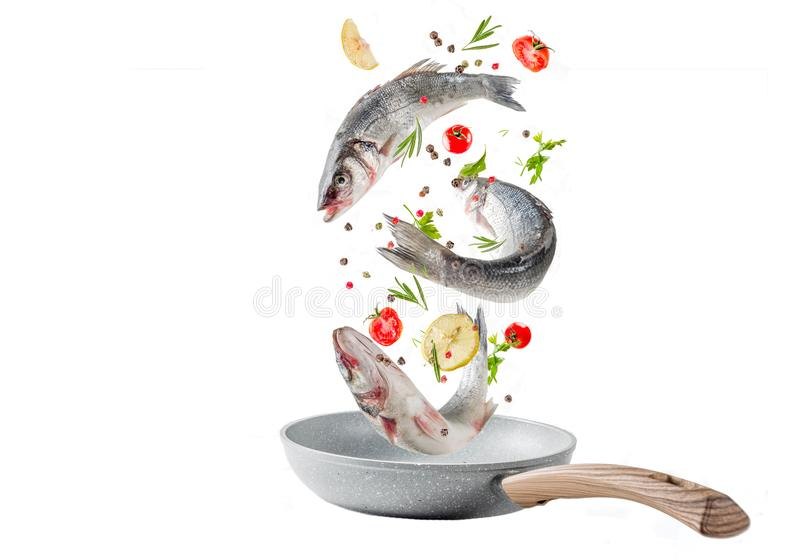 Flying food, raw sea bass fish with spices. Raw sea bass fish with spices and ingredients, ready for cooking, with frying pan. Flying food isolate on white royalty free stock photography