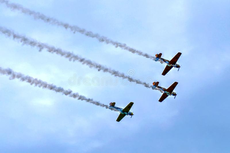 Flying in formation - planes at acrobatic show. 3 small military aircrafts with propellers flying in formation, with smoke trails, at aero acrobatic show royalty free stock photography