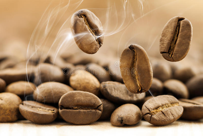 Flying fresh coffee beans as a background with copy space. Coffee beans falling down with white steam vapour. royalty free stock photography