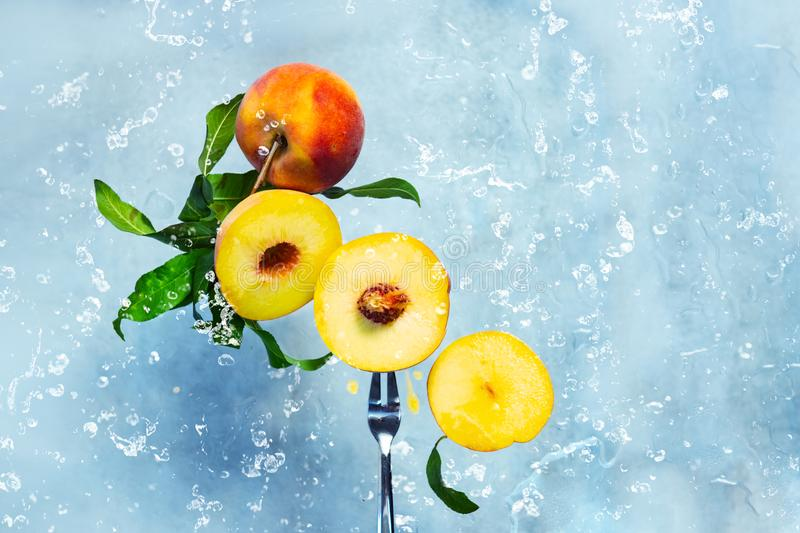 Flying fresh ripe peach with green leaves on blue background. food levitation. With water splashes. Juicy concept healthy eating stock image