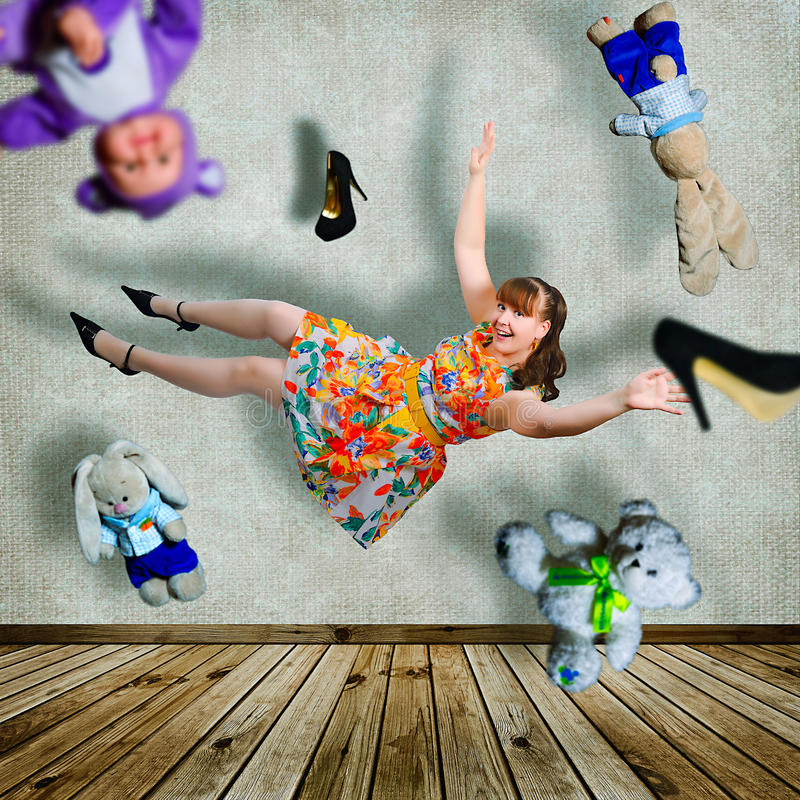 Flying girl. Collage with girl flying around the room. She has long dark hair. Bright colored dress. On the legs white stockings and black shoes. The room just stock image