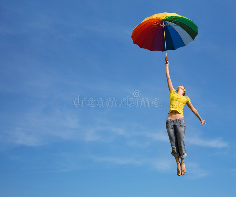 Flying girl with colorful umbrella in the blue blu stock image