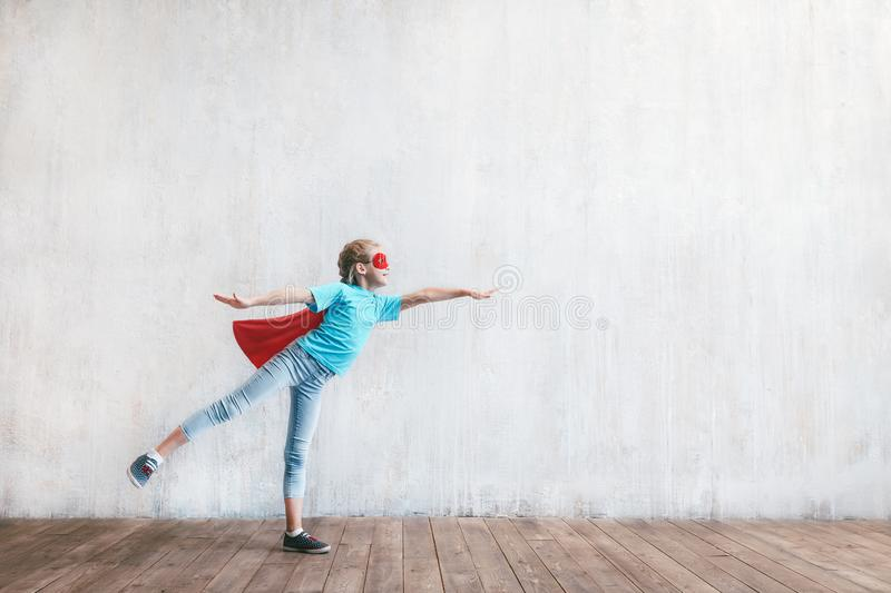 Flying girl hero with a cloak. In the studio stock photo
