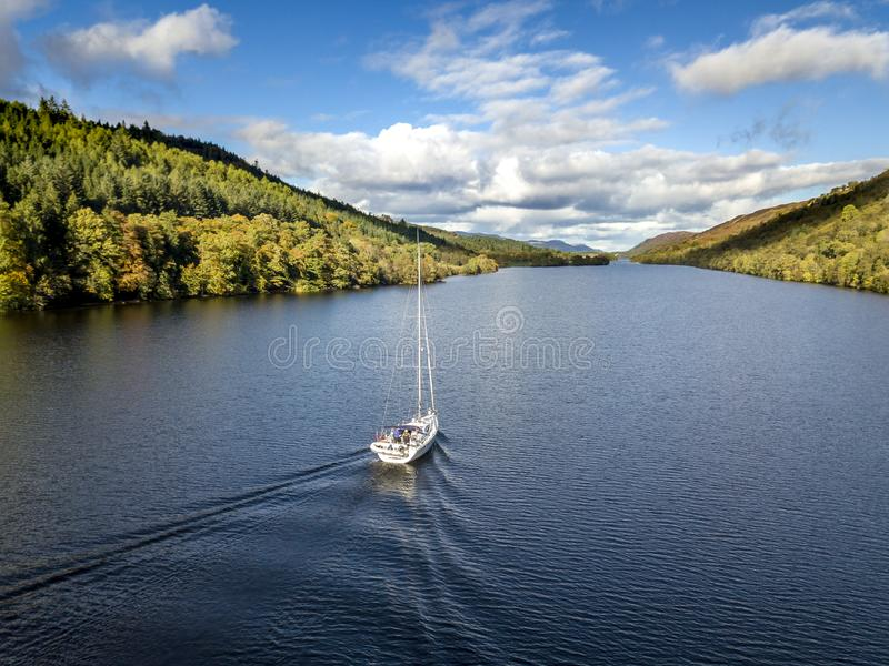 Flying through the Great Glen above Loch Oich towards Loch Ness behind a white motor yacht in the scottish highlands -. United Kingdom royalty free stock image