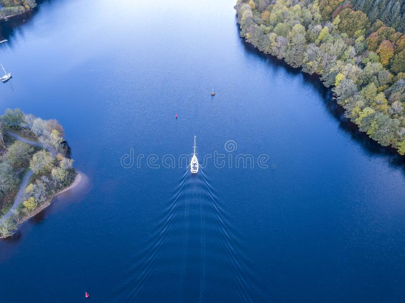 Flying through the Great Glen above Loch Oich towards Loch Ness behind a white motor yacht in the scottish highlands -. United Kingdom royalty free stock photography