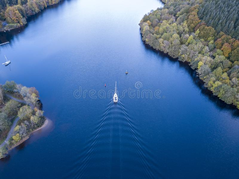 Flying through the Great Glen above Loch Oich towards Loch Ness behind a white motor yacht in the scottish highlands -. United Kingdom royalty free stock photos
