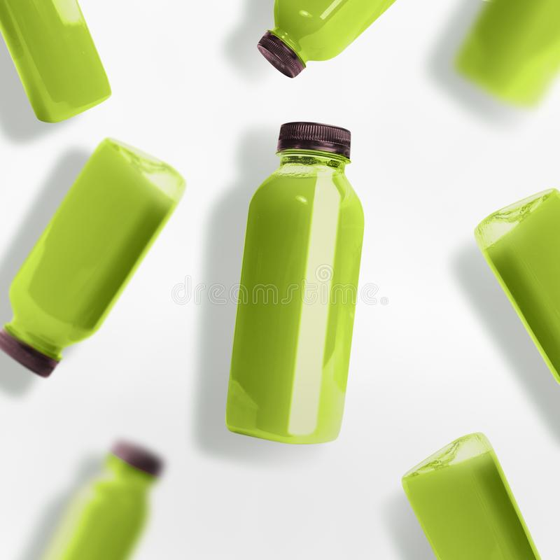 Flying green smoothie or juice bottles pattern on white background, top view. Branding copy space royalty free stock photo