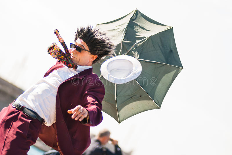 Flying hat and umbrella. Comedian guy with fake flying hat and broken umbrella at Barcolana village - Barcolana sailboat race - Trieste (Italy) 2007 stock photos