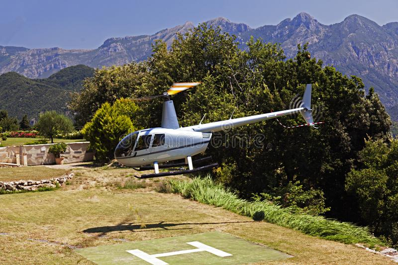 A flying helicopter in a beautiful garden of a luxury hotel in Italy royalty free stock photography