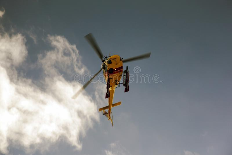 A flying helicopter in the blue sky royalty free stock images