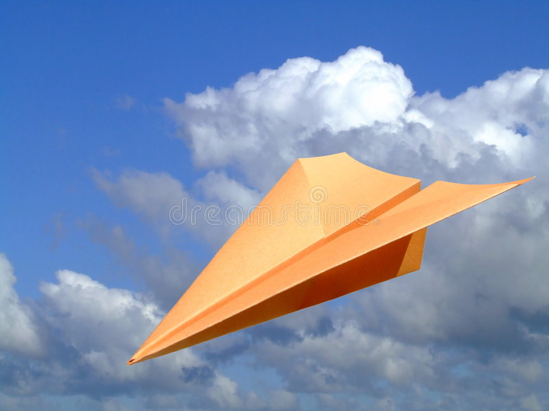 Flying High. A paper plane with a background of blue sky and clouds stock photography