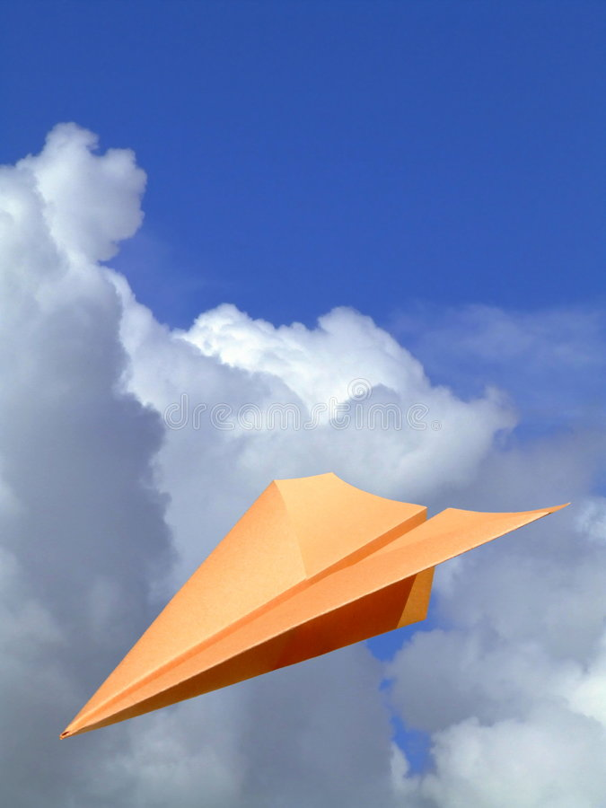 Flying High. A paper plane with a background of blue sky and clouds royalty free stock images