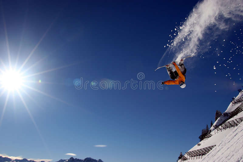 Flying High. A Snowboarder is flying high in front of the blue sky and sun